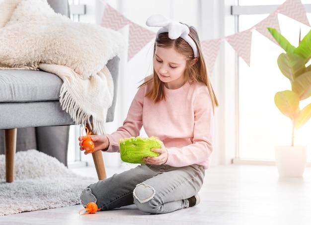Bambina seduta sul pavimento a casa e tenendo il cesto verde e l'uovo dipinto nelle sue mani al giorno di pasqua