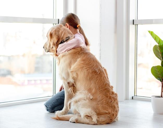 Bambina seduta sul pavimento accanto alla finestra panoramica con il cane golden retriever e abbracciandolo