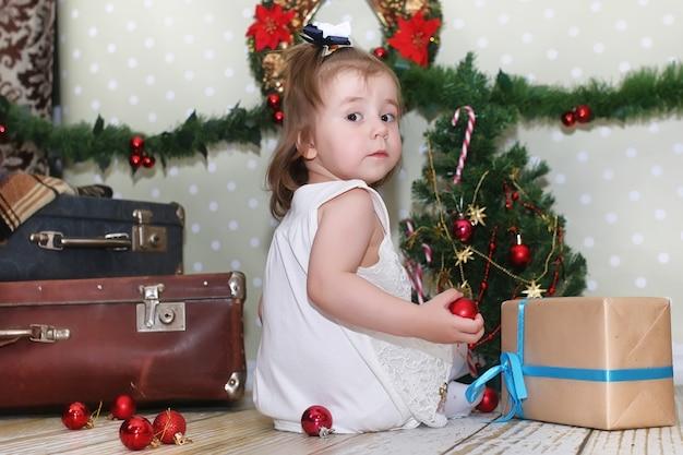 Bambina seduta davanti a un albero di natale e gioca con i giocattoli