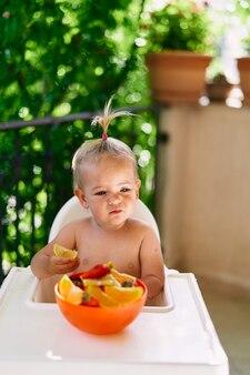 Bambina seduta su un seggiolone con una fetta d'arancia in mano