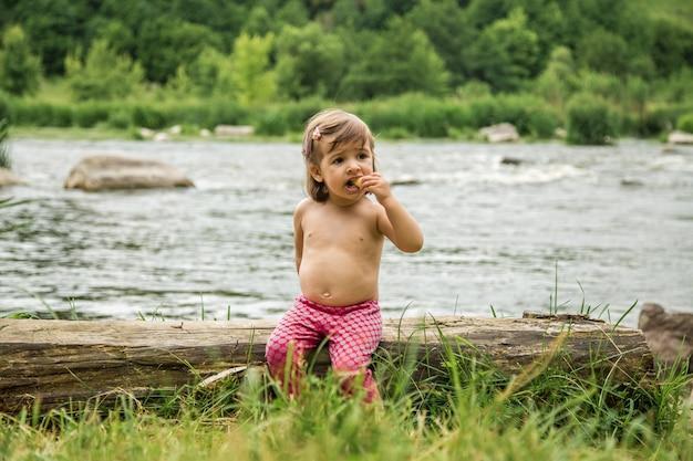 Bambina seduta su un tronco vicino al fiume