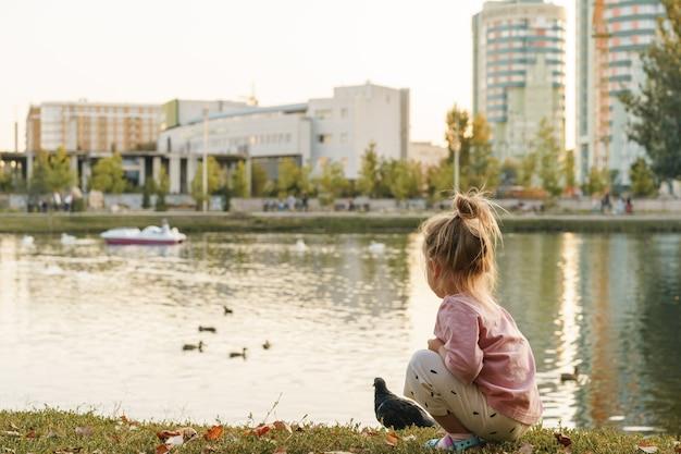 Bambina seduta nel parco vicino al lago
