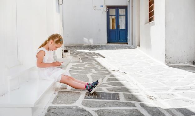 Bambina che si siede sotto il portico, grecia
