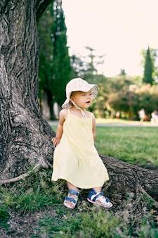 Bambina seduta sulle radici di un enorme albero nel parco