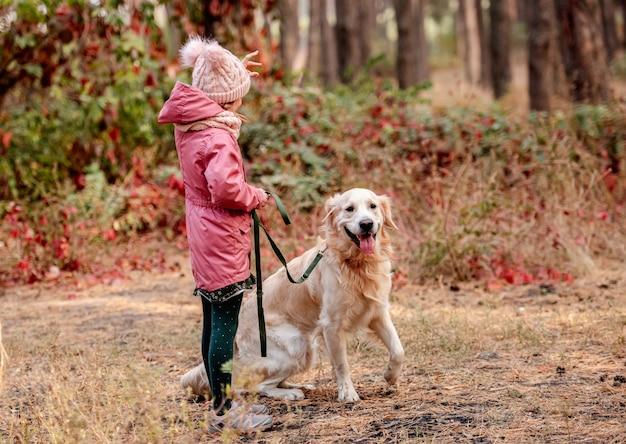 Bambina seduta lateralmente tenendo il guinzaglio del golden retriever nelle mani nella foresta di autunno