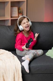 Bambina che si siede sul sofà che gioca un video in salone a casa. joystick emozionante della tenuta della mano della ragazza del giocatore che gioca il gioco a console usando un regolatore senza fili.