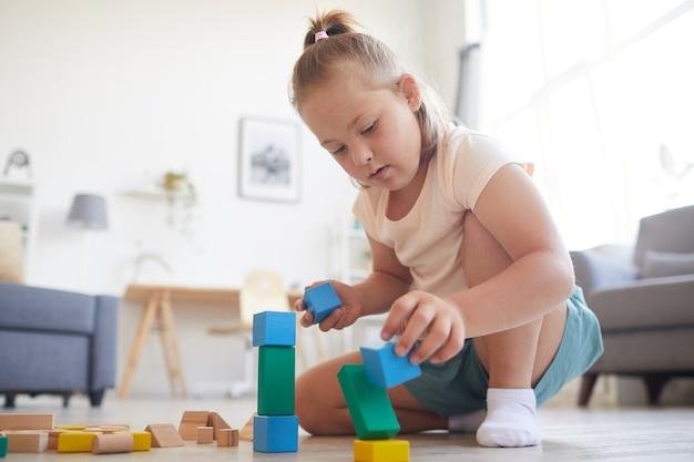 Bambina seduta sul divano e giocando con i blocchi colorati sta costruendo una piramide a casa