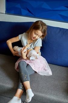 Bambina seduta sul divano nella stanza di casa che gioca con la bambolina, canta una canzone, come la mamma.