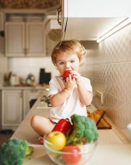Bambina seduta sul tavolo e mangia il pomodoro