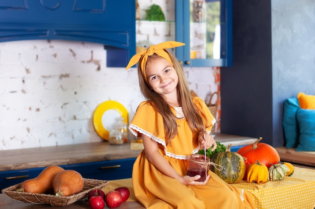 La bambina che si siede sulla superficie di lavoro della cucina sta aspettando la colazione con il barattolo di inceppamento. bambino allegro e cattivo in cucina. cucina interna con zucche, mele. mangiare sano. decorazioni autunnali