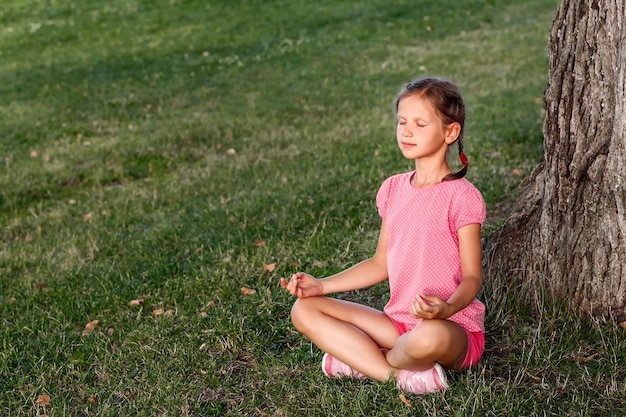 Bambina seduta in una posa yoga sull'erba