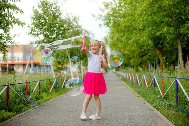 Bambina che fa skateboard nel parco in estate