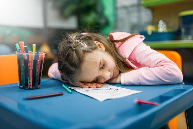 La bambina dorme nell'area giochi dopo il disegno, negozio di animali. bambino stanco in negozio di animali, merci per clienti e animali domestici