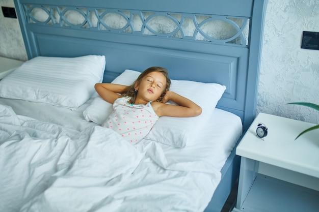 Bambina che dorme su una biancheria bianca da letto grande e accogliente nel pomeriggio a casa, stile di vita familiare, cuscino comodo, letto