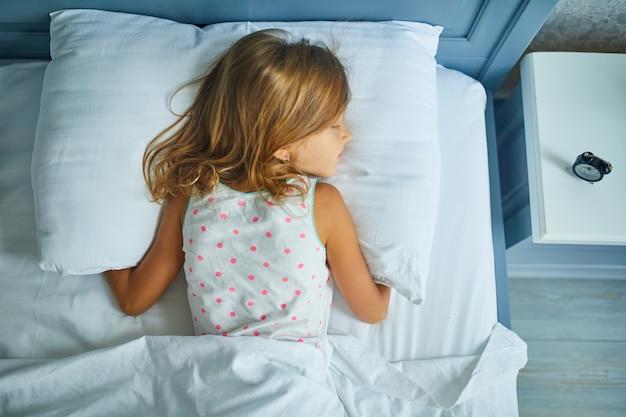 Bambina che dorme su una biancheria bianca da letto grande e accogliente nel pomeriggio a casa