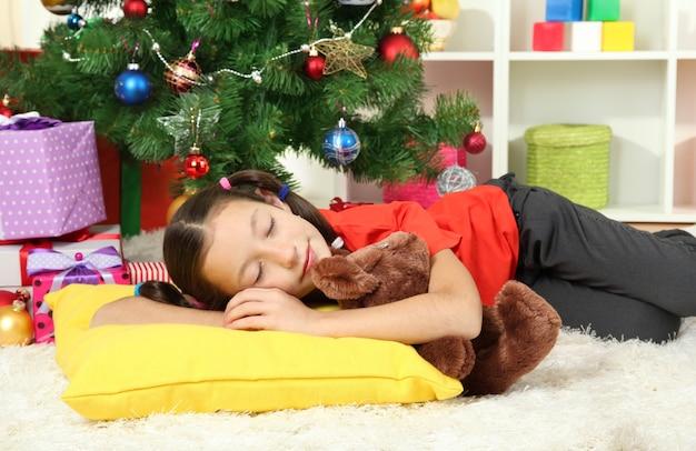 Bambina che dorme vicino all'albero di natale