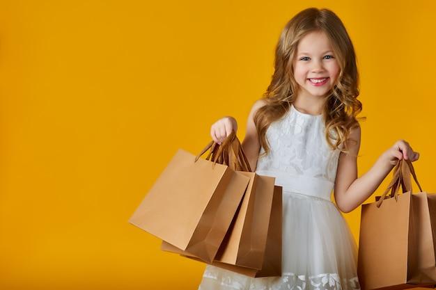 Sorriso della bambina con i sacchetti della spesa su colore giallo
