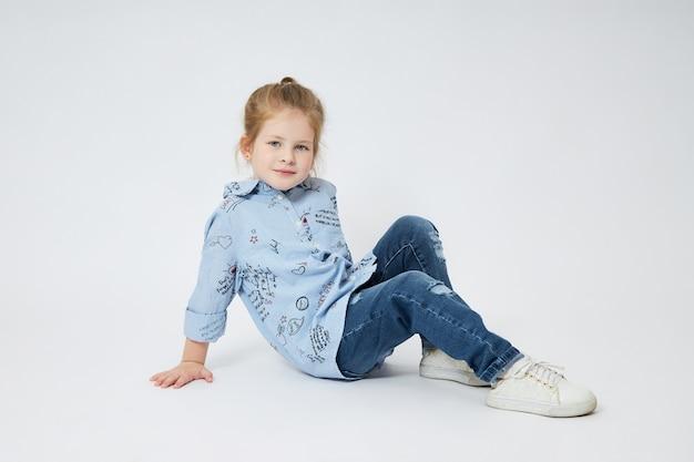 La bambina sorride. bambino in abiti autunnali pone su bianco