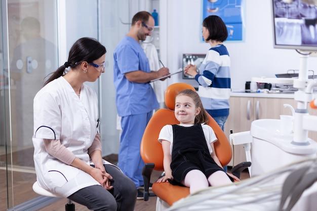Bambina che sorride al dentista che si siede sulla sedia che aspetta il trattamento dei denti. bambino con sua madre durante il controllo dei denti con stomatolog seduto su una sedia.