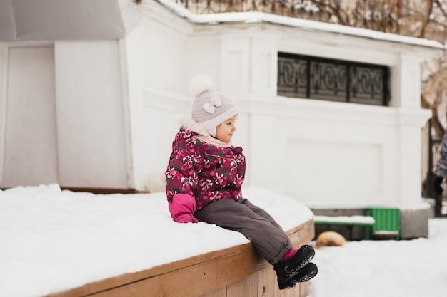 Bambina che sorride e che si siede in scena, inverno