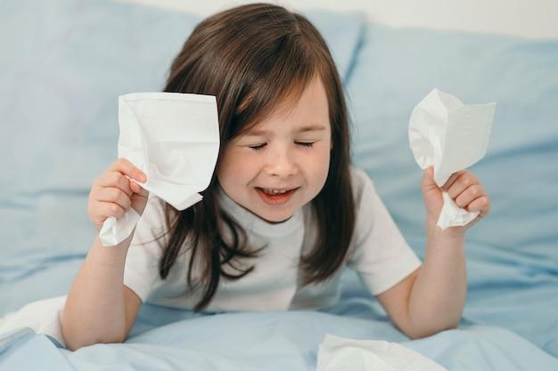 Una bambina starnutisce. il bambino ha il raffreddore e viene curato a casa. la ragazza è sdraiata su un letto con lenzuola blu.