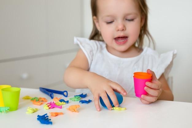 Una bambina ordina le figure degli animali in base al colore, gettandole nella tazza appropriata.