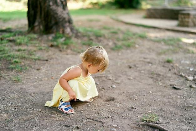 Bambina accovacciata vicino a un buco nel terreno vicino a un albero