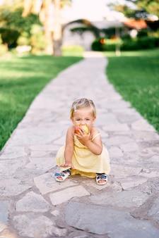 Bambina accovacciata su un sentiero lastricato nel parco e rosicchiare una mela