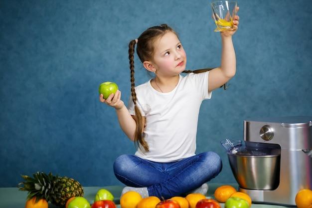 La bambina ha spremuto il succo fresco dalla frutta delle mele e dell'arancia. vitamine e alimentazione sana per i bambini.
