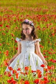 Bambina in piedi in un campo fiorito