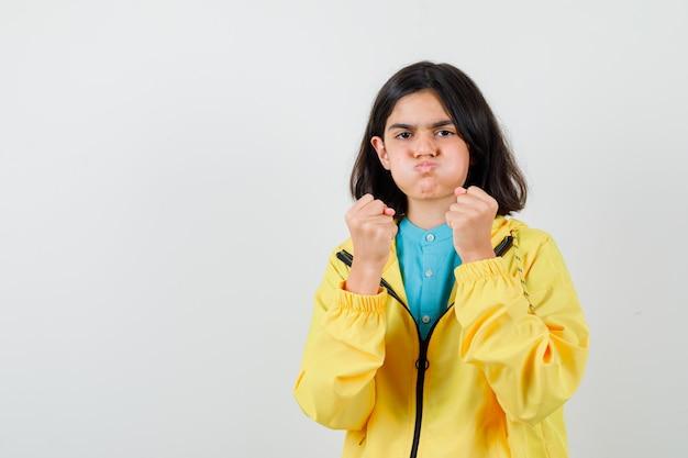 Bambina in piedi in posa di combattimento mentre soffia le guance in camicia, giacca e sembra sicura. vista frontale.