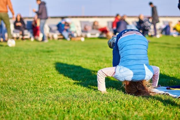 Bambina in piedi sulla sua testa sull'erba nel parco