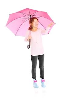 Una bambina in piedi con un ombrello su sfondo bianco