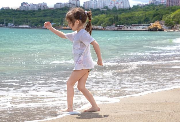 Una bambina sta a piedi nudi in riva al mare e bagna i piedi nell'onda del mare.