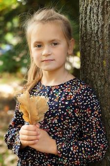 Bambina si trova in un parco cittadino e tiene in mano una quercia. passeggiate autunnali.
