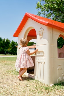 La bambina sta all'ingresso della casa dei giocattoli nel parco giochi