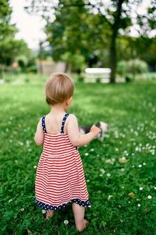 La bambina sta su una vista posteriore del prato fiorito
