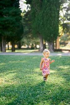 La bambina sta su un prato verde nel parco