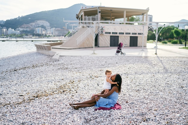 La bambina sta in piedi e abbraccia la mamma seduta sulla spiaggia