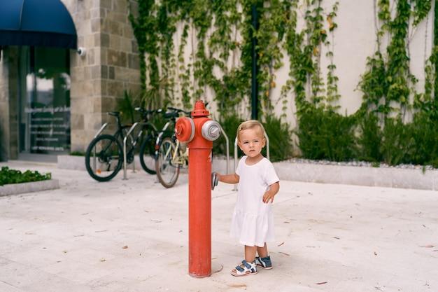 La bambina sta vicino a un idrante antincendio per strada