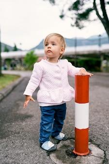 La bambina sta vicino a un pilastro a strisce sull'asfalto in un parco verde