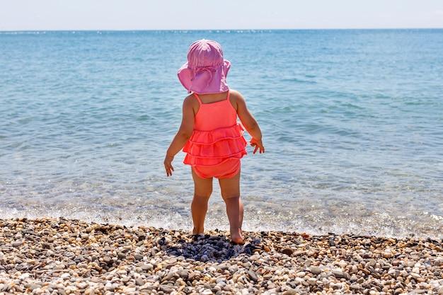 Una bambina sta nell'acqua e guarda il mare sulla spiaggia in estate. copia spazio per il testo