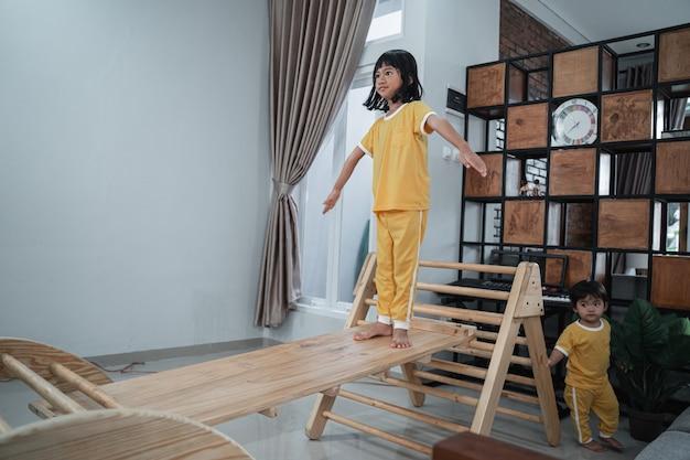 Una bambina sta con le braccia tese su un giocattolo a triangolo pikler mentre gioca a casa