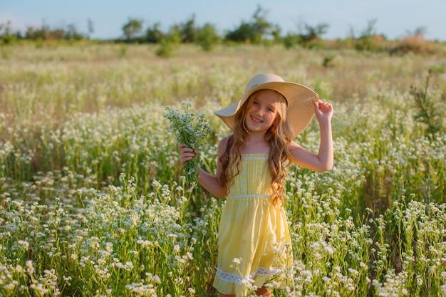 Bambina in un cappello di paglia nel campo