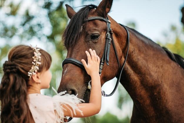 Una bambina accarezza un cavallo sulla testa del suo cavallo preferito