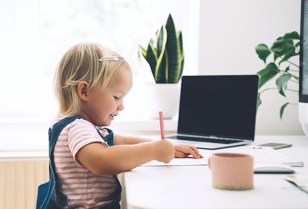 Bambina che studia e disegna alla scrivania apprendimento online per bambini