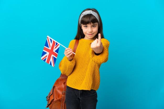 Bambina che studia inglese isolata su sfondo blu facendo un gesto imminente