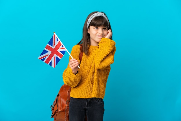 Bambina che studia inglese isolato su sfondo blu frustrato e che copre le orecchie