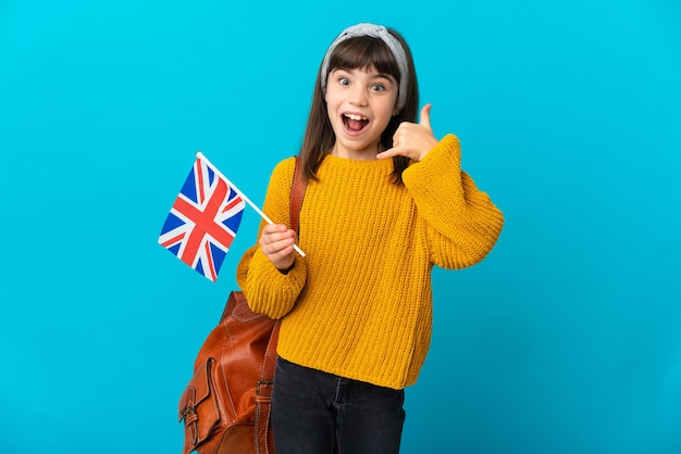 Bambina che studia inglese isolato su sfondo blu che fa il gesto del telefono. richiamami segno