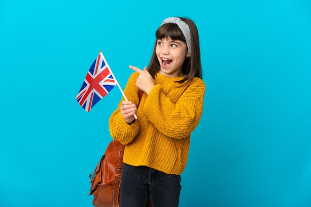 Bambina che studia inglese isolato sulla parete blu che intende realizzare la soluzione sollevando un dito